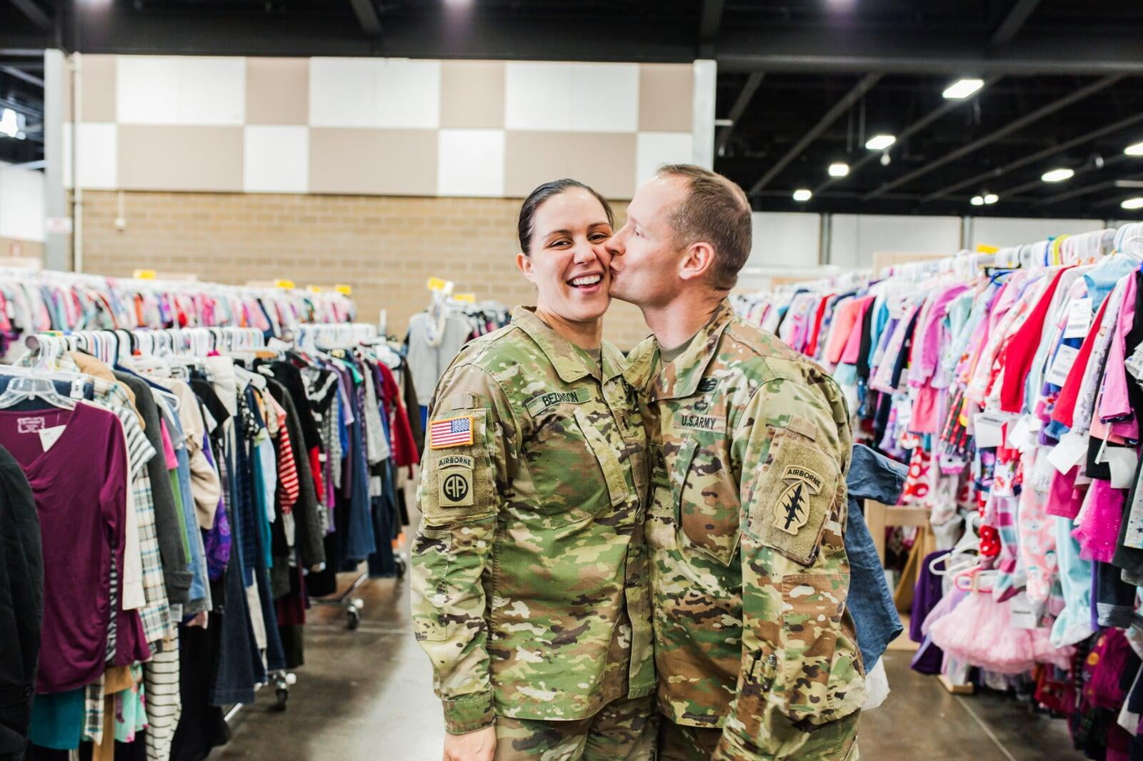 A military husband in camo kisses his military wife, also in camo, at the JBF sale in Tacoma Washington.