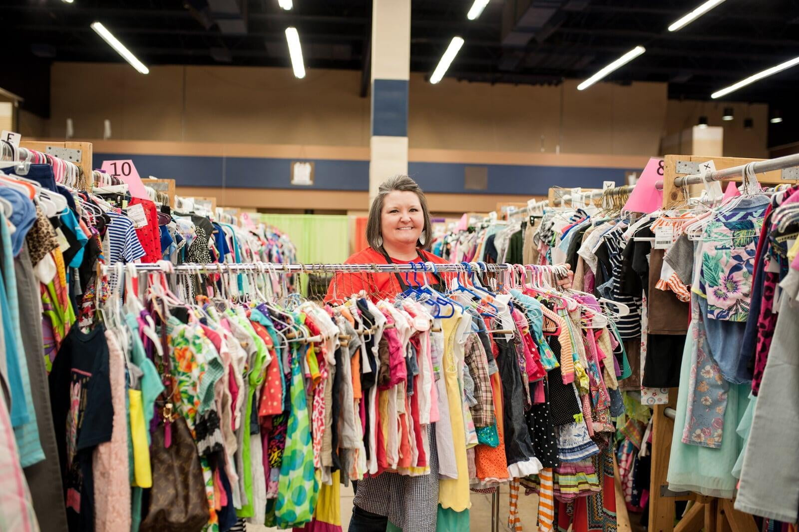A smiling Team Member stands behind a rack of toddler girl's clothing at the sale.